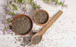 Dois potes cheios e uma colher também cheia de sementes de chia sobre uma mesa nude. Além disso, há flores para ornamentar