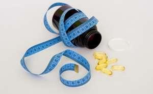 frasco de comprimidos na cor preta envolvido por fita métrica de medidas e comprimidos transparentes de ômega 3
