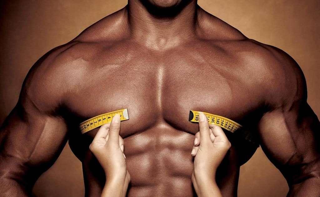 corpo bronzeada de um homem extremamente musculoso e mãos femininas segurando uma fita métrica que não consegue ser fechada no busto do rapaz pela grande concentração de músculos