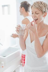 Mulher loira, com camiseta branca de alça, levando a boca um comprimido de Sibuterol entre os dedos de uma das mãos. A outra mão, está segurando um copo com água.
